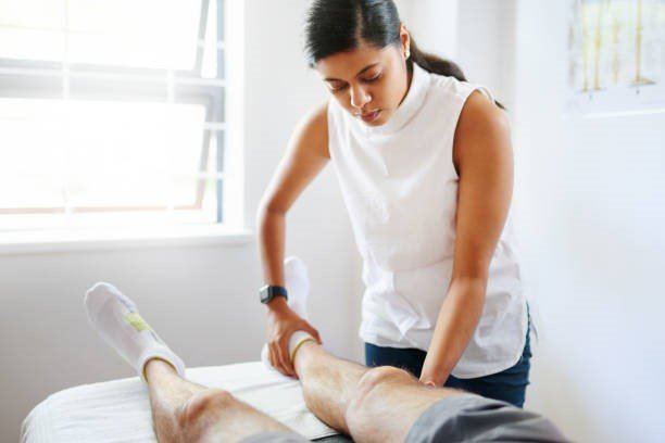 physiotherapist doing leg exercises with her patient